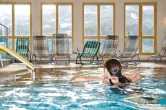 Woman in spa pool. Woman swimming in indoor spa pool with alpine mountain view Royalty Free Stock Image