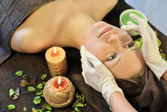Woman on SPA procedures. Young woman in beauty shop taking face massage Stock Photos