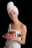 Woman with spa products. Woman with towel with spa products over black royalty free stock photos