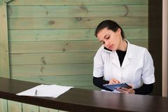 Woman in a spa recpetion uses tablet pc texting to client. Beauty and technology concept. stock photo