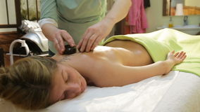 Woman in spa salon with hot stones stock video footage