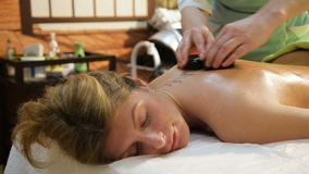 Woman in spa salon with hot stones stock video