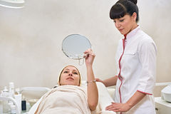 Woman in spa salon with mirror Royalty Free Stock Photos