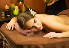 Woman in spa salon with orchid flower in her hair Royalty Free Stock Photo