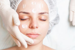 Woman in spa salon receiving face treatment with facial cream Stock Photo