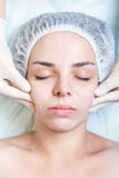 Woman in spa salon receiving face treatment with facial cream Royalty Free Stock Photography