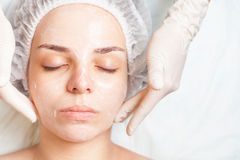Woman in spa salon receiving face treatment with facial cream. Beautiful young woman in spa salon receiving face treatment with facial cream at white background Royalty Free Stock Photos