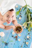Woman in spa salon. Smiling young woman with cup of herbal tea in bath towel in spa salon. Herbal treatment Stock Photography