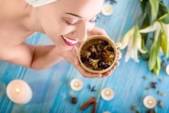 Woman in spa salon. Smiling young woman with cup of herbal tea in bath towel in spa salon. Herbal treatment Royalty Free Stock Photo