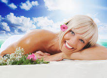 Woman in a spa salon. Young beautiful woman in a spa salon massage procedure on sunny tropical beach on the island paradise in the middle of the sea stock photos