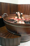 Woman at a Spa Soaking in a Large Wooden Bathtub Royalty Free Stock Photography