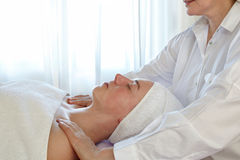 Woman In Spa With Therapsist. Woman with a white towel around her head relaxing on a table in a spa while a female therapist massages her shoulders during Royalty Free Stock Image