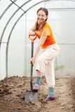 Woman with spade in greenhouse Royalty Free Stock Image