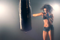 Woman sparring punching bag in gym Stock Images