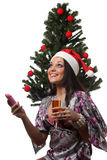Woman speak mobile in front of a christmas tree Stock Images