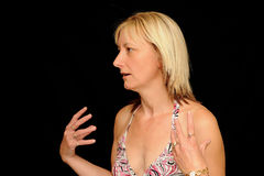Woman speaking. A portrait of a middle-aged woman speaking and gesturing as if in conversation, isolated on a black background royalty free stock photo