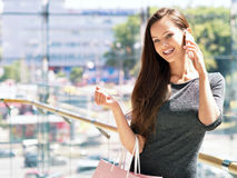 Woman speaking by cell mobile phone with shopping bags Royalty Free Stock Photography