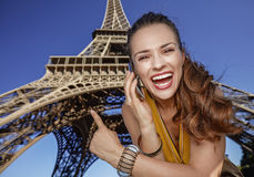 Woman speaking on cell phone and pointing against Eiffel tower Royalty Free Stock Image