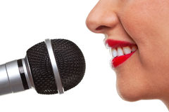 Woman speaking into a microphone. Close up of a woman using a microphone, isolated on a white background Royalty Free Stock Image