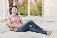 Woman speaking on mobile phone on couch Royalty Free Stock Photo