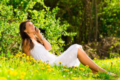 Woman speaking on a mobile phone on the grass Royalty Free Stock Photography