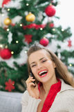 Woman speaking mobile phone near Christmas tree Stock Image