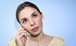 Woman is speaking by mobilephone. Smiling woman with phone. On blue background Royalty Free Stock Image