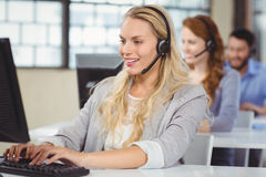 Woman speaking over headset while working Stock Images