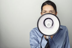 Woman speaking over a megaphone. As she makes a public address, participates in a protest or organises a rally or promotion, over grey with copyspace to the Royalty Free Stock Image