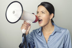 Woman speaking over a megaphone. As she makes a public address, participates in a protest or organises a rally or promotion, over grey with copyspace to the Royalty Free Stock Images