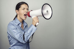 Woman speaking over a megaphone Royalty Free Stock Photos