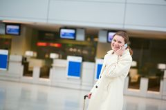 Woman speaking on the phone in the airport Stock Image