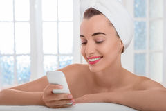 Woman speaking phone in the bathroom or spa salon. Young smiling and naked woman with towel on her head speaking phone in the bathroom or spa salon Stock Photos