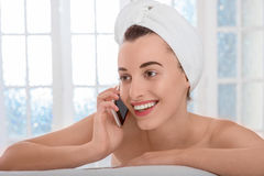 Woman speaking phone in the bathroom or spa salon Royalty Free Stock Photos