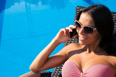 Woman speaking by phone on deckchair Stock Photo