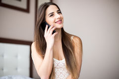 Woman speaking on the phone while laying on the bed at home Stock Photos