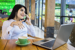 Woman speaking on the phone at restaurant Royalty Free Stock Photography