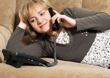 The woman speaking by phone on a sofa Stock Images