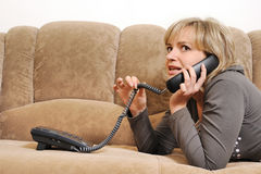 The woman speaking by phone on a sofa Stock Image