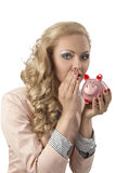 Woman speaking with piggybank. Beutiful blonde woman with curly hair-style wearing business suit and taking piggybank in the hand. She speaking with that Stock Images