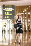 Woman speaking on smartphone in airport Stock Photo