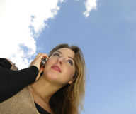 Woman speaks. Young woman speaks by mobile phone on background of sky stock photography