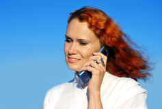 Woman speaks mobile phone. Young woman speaks mobile phone on a blue sky background Royalty Free Stock Images