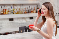 Woman speaks over the phone in bar Royalty Free Stock Images