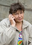 The woman speaks on the phone. The elderly woman speaks on the phone royalty free stock photography