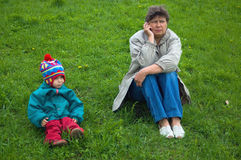 The woman speaks on the phone, the girl sits next. On a grass royalty free stock photo