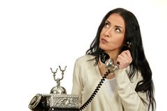 Woman speaks on a vintage phone.She is thinging. Stock Photo