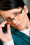 Woman in spectacles. Portrait of young woman looking over top of glasses or spectacles Royalty Free Stock Photo