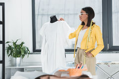 Woman in spectacles and measuring tape on neck looking at fashionable white dress on dummy. Young woman in spectacles and measuring tape on neck looking at Stock Photography