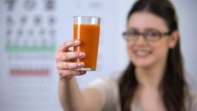 Woman in spectacles showing glass with carrot juice, beta carotene, vitamins. Stock footage stock video footage